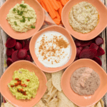 Make the ultimate Plant Paradox party platter with 5 different dip recipes: cauliflower hummus, black bean hummus, artichoke pesto, classic guacamole, and fruit dip.