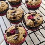 Chocolate chip raspberry muffins cooling on a rack.